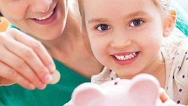 Kleines Mädchen beim Geld sparen